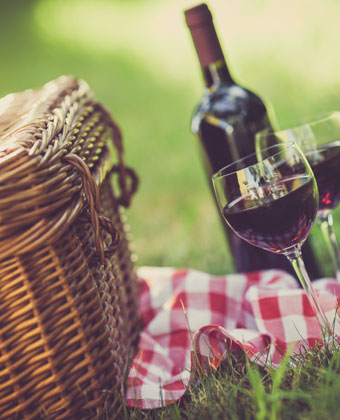 Picnic basket with wine glasses and red wine