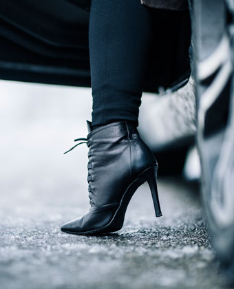 woman in boots stepping out of car